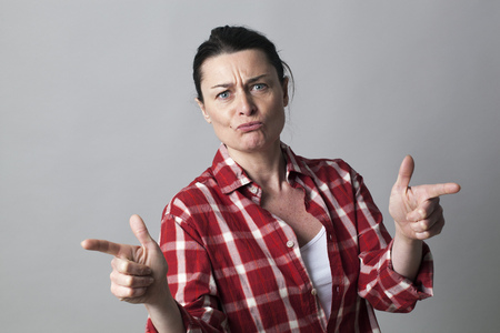 provoking: unhappy middle aged woman defending herself with fighting hand gestures with fingers shooting like guns in the foreground Stock Photo