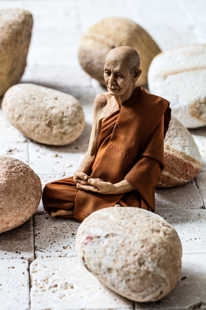inner peace: mindfulness concept - lonely yogi man sitting on white limestone with round beige pebbles for serenity, inner peace and meditation