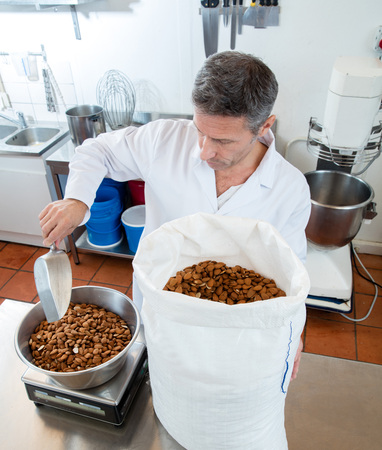 weighting: French male craftsman picking from a big bag and weighting fresh almonds for sweet nougat specialty, industrial cuisine background Stock Photo