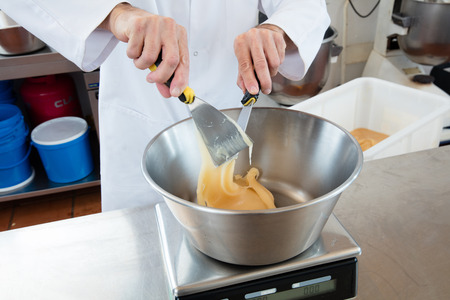 weighting: male cook hands weighting honey with a spatula to scale onto an industrial bowl for sweet nougat specialty, commercial laboratory background Stock Photo