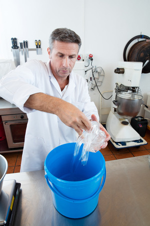 scaling: preparation of dose of glucose for French sweet nougat specialty by male craftsman, scaling sugar material from a bucket, industrial laboratory background
