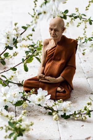 yogi: mindfulness concept - old yogi man sitting on white limestone background with fresh white spring blossom flowers for meditation or spiritual retreat Stock Photo