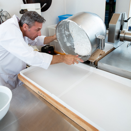 man nuts: pouring of mixture of Italian white dough with roasted almonds for French sweet nougat specialty by male craftsman in industrial laboratory Stock Photo