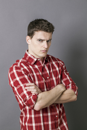 exasperation: bored young sportsman with arms folded, looking depressed and irritated, wearing a casual red checked shirt over grey background