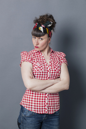 exasperation: sulking brunette woman with retro hairstyle and fifties look crossing her arms to express her disagreement, pouting her anger and exasperation over grey background Stock Photo