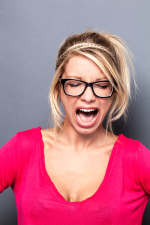 exasperation: mad young sexy blond woman with eyeglasses shouting her exasperation, complaining or expressing her frustration over grey background Stock Photo