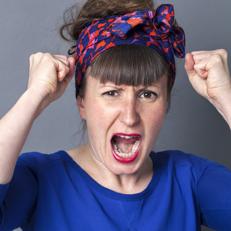exasperation: portrait of a furious childish woman with bangs and a fifties scarf as retro hairstyle shouting with fists up, being enraged and exasperated over grey background Stock Photo