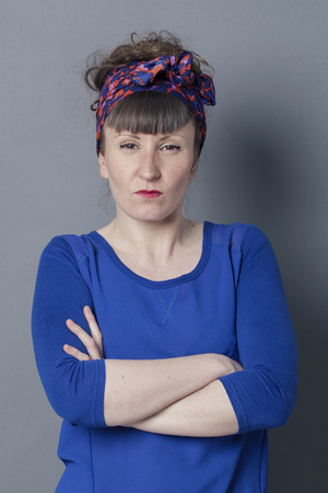 exasperation: unhappy brunette woman with bangs and a fifties scarf as old fashioned hairstyle crossing her arms, staring to express her frustration and exasperation over grey background Stock Photo