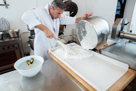 incorporation: pouring of Italian white dough with roasted almonds for French sweet nougat specialty by male pastry cook in commercial kitchen