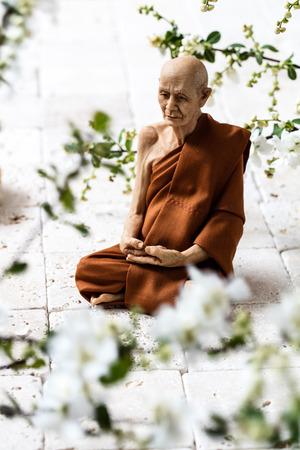 paz interior: atención concepto - hombre yogui solo que se sienta en piedra caliza blanca fresca blanca flor de las flores de primavera para la relajación o la paz interior