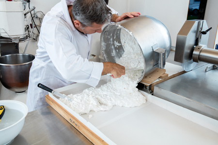 incorporation: spreading of Italian white dough with roasted almonds for French sweet nougat recipe by male pastry cook in stainless steel kitchen