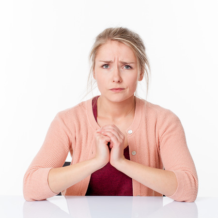 disappointed young blond woman expressing herself with confused hands held together, frowning her frustration over a white office background