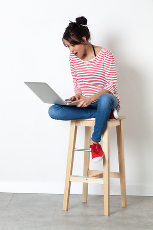 laughing beautiful multi-ethnic young woman relaxing on a stool, expressing surprise in communicating through her laptop  in summertime, white background indoors