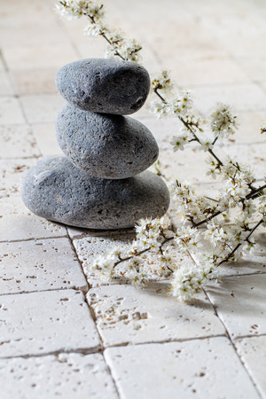 inner beauty: zen detox still-life - three stones in balance with fresh white spring flowers on mineral background for inner beauty or wellbeing concept