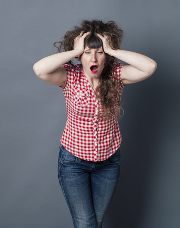 exasperation: bored brunette woman standing, holding her head and very long curly brown hair, yawning for mad hairstyle over grey background