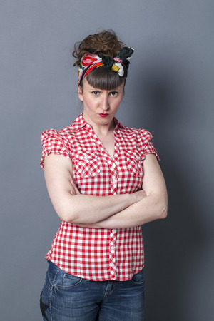 exasperation: sulking brunette woman with bangs and a fifties scarf as old fashioned hairstyle folding her arms, pouting to express her anger and exasperation over grey background Stock Photo