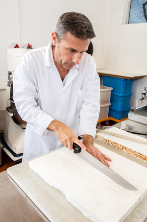 industrial kitchen: male cook cutting hand-made nougat made of Italian white dough with roasted almonds, honey and edible rice paper in industrial kitchen