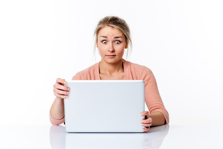 amazed young blond woman sitting at a clean white desk, staring at her computer screen with eyes wide open for surprising job, isolated white background studio