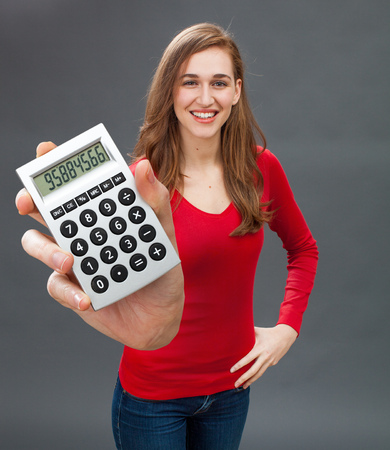 emphasized: smiling beautiful young woman standing, expressing financial success, economic serenity or having a positive figure on her emphasized calculator in the foreground Stock Photo