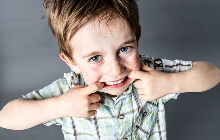 misbehavior: happy red hair young kid standing, making a funny face with his big mouth for cheeky misbehavior, high angle view, grey background