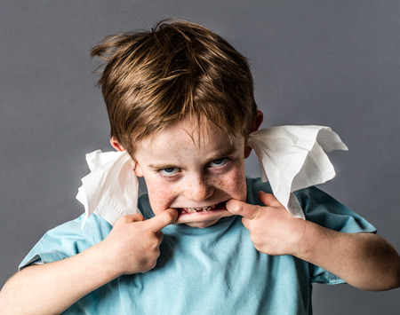 misbehavior: silly 5-year old red hair kid making a grimace with his big mouth, not listening with tissue in both ears for confronting misbehavior, contrast effects on grey background Stock Photo