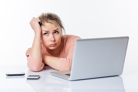 disillusioned: disillusioned beautiful blond girl blowing out her cheeks, lying on her white sparse desk, studying hard on her laptop thinking about her career, isolated white background Stock Photo