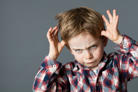 mocking: rude red hair young kid mocking and teasing, playing with his hands making a face for stubborn and determined attitude, grey background