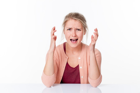 exasperation: mad young blond woman expressing herself with nervous hands up, shouting her stress and anxiety over a white office background
