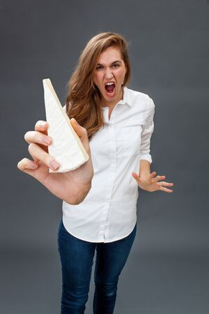 tantrum: furious young beautiful woman having a tantrum in holding an unhealthy dairy product in her hand in the foreground for allergies or diet warning Stock Photo