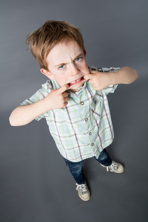 misbehave: unhappy red hair young boy standing, making a grimace with his big mouth for determined attitude, high angle view, grey background