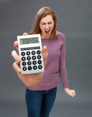 enraged: enraged young woman standing with a nervous fist, screaming against financial economy or the wrong figures on her oversized calculator in the foreground