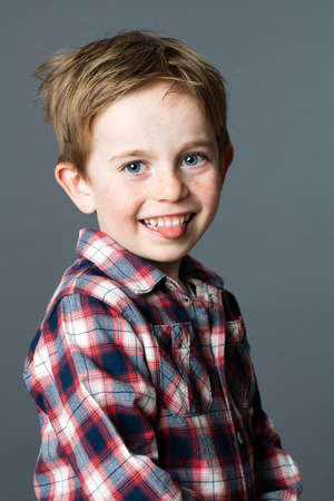 portrait of a beautiful wise little boy with big blue eyes enjoying sticking out his tongue for fun, making a face for cheeky attitude, grey background Stock Photo