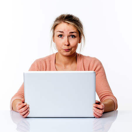 dubious: dubious beautiful young blond female university student sitting at a clean white desk, thinking about her career facing her laptop screen to study and work, isolated white background studio