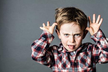 дети: сердитый маленький брат, наслаждаясь делает гримасу, выпятив язык, играя с его руки за плохое поведение, эффект контраста, серый фон