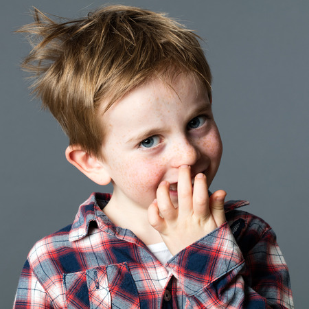 mischievous: cheeky little red hair kid with freckles picking his nose to provoke and act mischievous for fun gesture and education, grey background