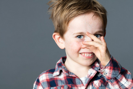 mischievous: beautiful young boy with blue eyes enjoying making a funny face playing with his hands for mischievous attitude and humor, grey background Stock Photo