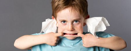 misbehave: playful 6-year old red hair boy with blue eyes playing with his mouth for grimace, not listening with tissue in both ears for misbehavior, grey background Stock Photo