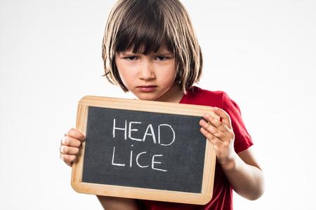 piojos: niño pequeño infeliz sosteniendo una pizarra en la escuela como un escudo contra los piojos información para la protección del niño en edad preescolar de la salud, estudio de fondo blanco