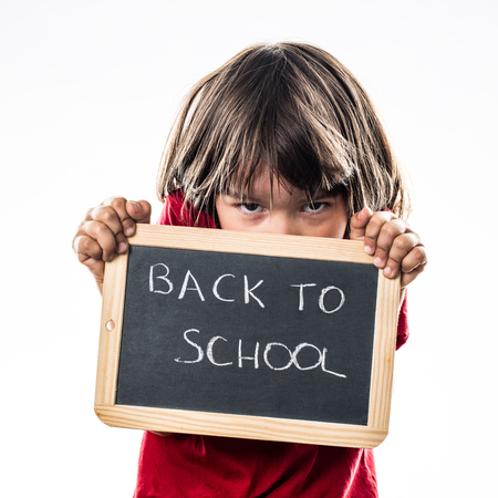 warning back: bullied little kid hiding behind a writing slate to protect against a scary back to school, white background studio