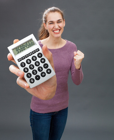 convinced: ecstatic beautiful young woman acting convinced and ambitious for her economic success, winning money in holding an oversized calculator in the foreground Stock Photo