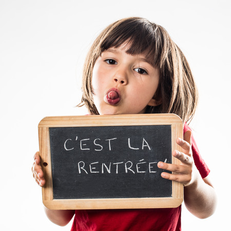 mischievous: mischievous beautiful young child sticking out her tongue for funny face, informing about a fun back to school on French writing slate, white background studio Stock Photo