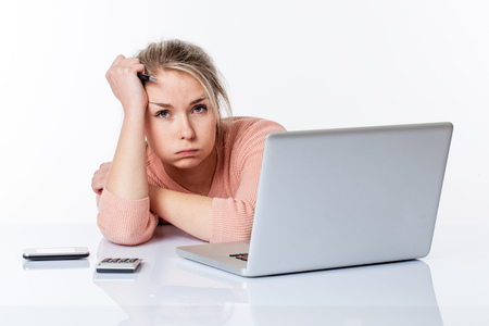 erschöpfte junge blonde Frau, ihre Wangen bläst, stützte sich auf ihrem weißen spärlichen Schreibtisch, Studium hart an ihrem Computer, isoliert auf weißem Hintergrund