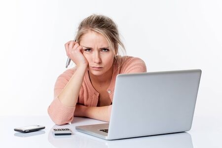 sparse: unhappy young blond woman leaning on her white sparse desk, complaining about studying or working on her laptop with communications technology, isolated white background