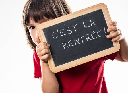 cheeky: cheeky young kid hiding behind a French writing slate, informing about a scary back to school, white background studio