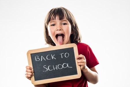 cheeky beautiful preschool child sticking out tongue to inform on a writing slate about a fun back to school, white background studio