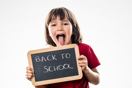 cheeky beautiful preschool child sticking out tongue to inform on a writing slate about a fun back to school, white background studio Фото со стока