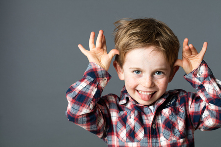 smiling young kid enjoying making a funny face, sticking out his tongue, playing with his hands for  fun childhood and humor, grey background