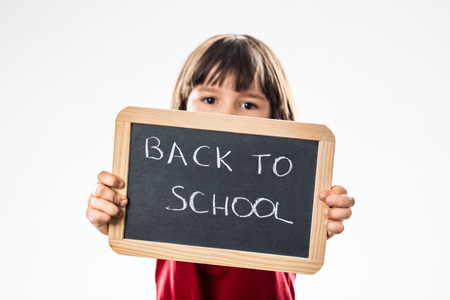 warning back: determined little child warning about back to school in showing a writing slate in the foreground, white background studio