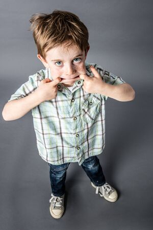 mischievous: standing red hair young boy enjoying making a funny face with his big mouth for mischievous misbehavior, high angle view, grey background Stock Photo