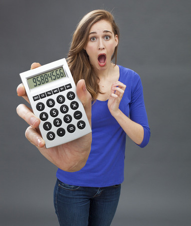 stunned: stunned beautiful young woman standing, expressing panic, mistake or shocking financial news in holding a big calculator in her hand in the foreground